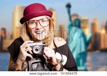 Girl in glasses with retro camera on New York background.