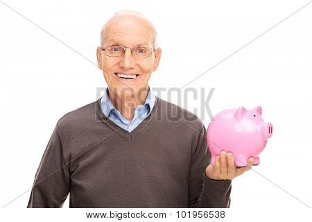 Cheerful senior gentleman holding a pink piggybank and looking at the camera isolated on white background