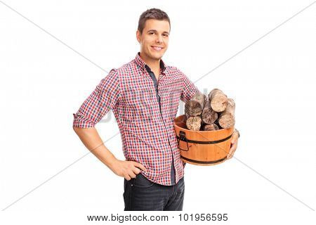 Cheerful young man holding a bucket full of logs isolated on white background