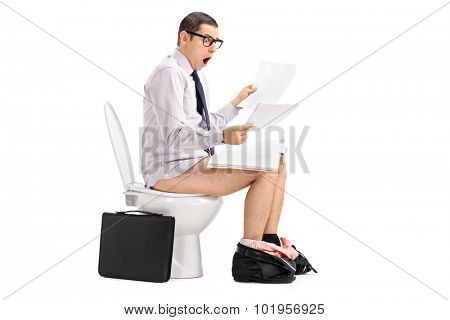 Shocked young businessman looking through some papers seated on a toilet isolated on white background