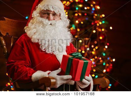 Santa Claus sitting on background of sparkling firtree