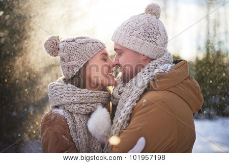 Young amorous couple in winterwear flirting outside
