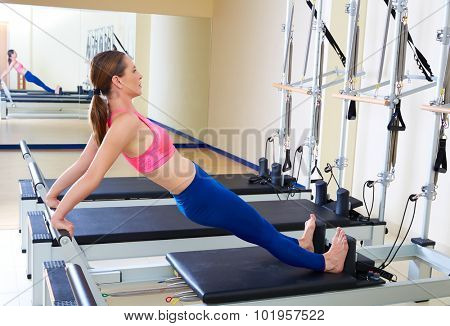 Pilates reformer woman long back stretch exercise workout at gym indoor