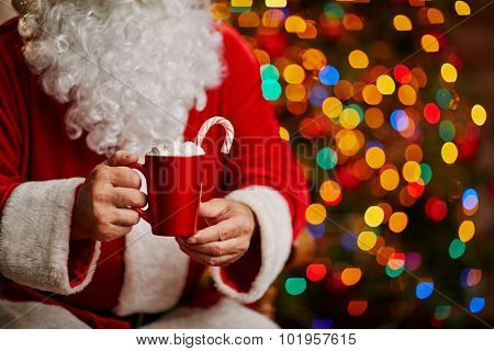 Tasty latte with whipped cream held by Santa