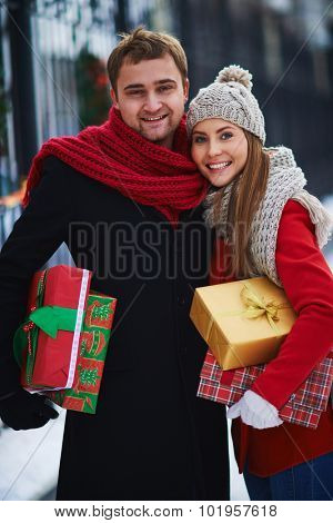 Amorous couple with giftboxes looking at camera outdoors