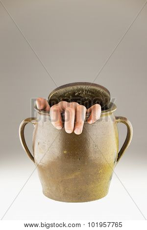Pot Covered With Half Dollar Coin And Man's Hand