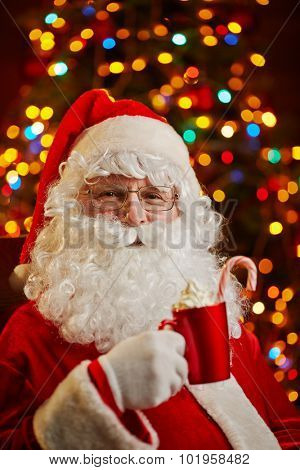 Santa Claus relaxing and having latte on background of Christmas tree