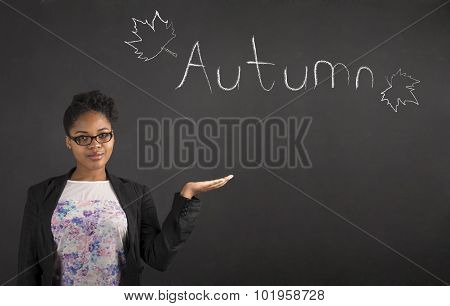 African Woman Holding Hand Out Showing Autumn On Blackboard Background