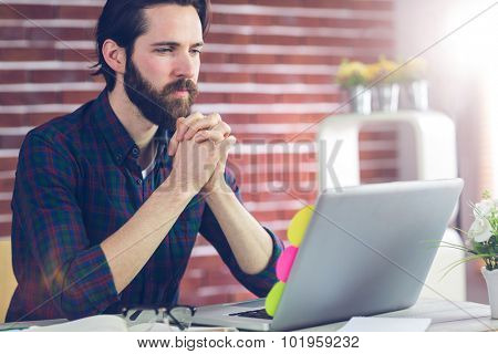 Focused editor with hand clasped using laptop in creative office