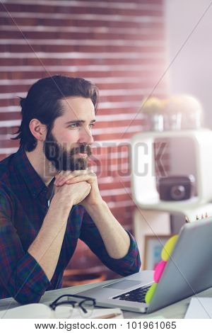 Thoughtful editor with hand clasped using laptop in creative office