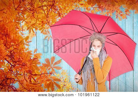 Woman blowing her nose with a tissue against autumn leaves pattern
