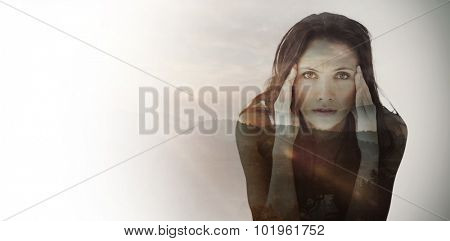 Portrait of upset woman with headache against trees and mountain range against cloudy sky