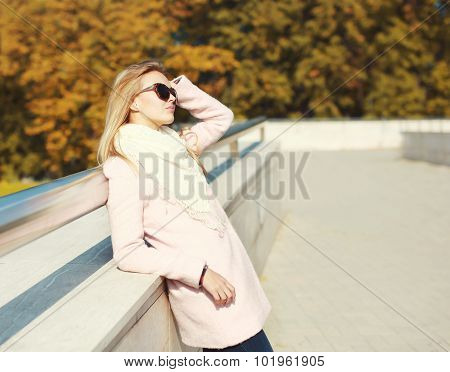 Beautiful Blonde Woman Wearing A Pink Coat With Sunglasses In Autumn City