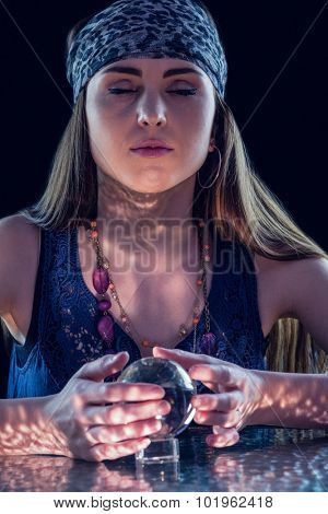 Fortune teller using crystal ball on black background