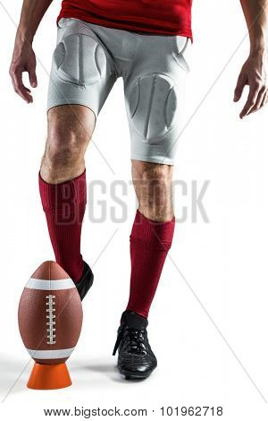 Low section of sports player kicking ball against white background