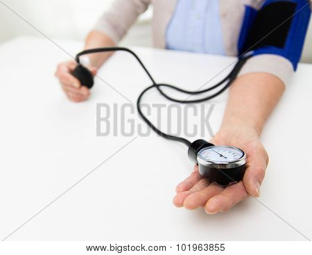 medicine, age, health care and people concept - close up of senior woman with tonometer checking blood pressure level at home