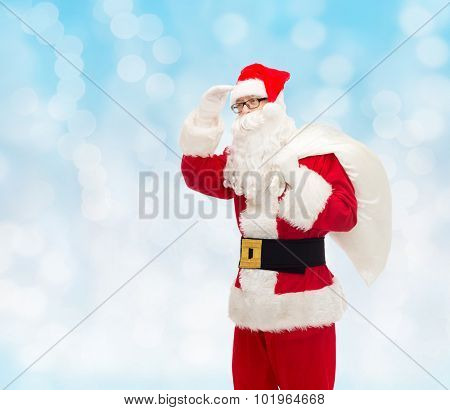 christmas, holidays and people concept - man in costume of santa claus with bag looking far away over blue lights background