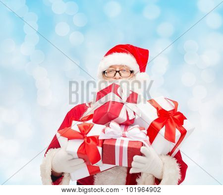 christmas, holidays and people concept - man in costume of santa claus with gift boxes over blue lights background