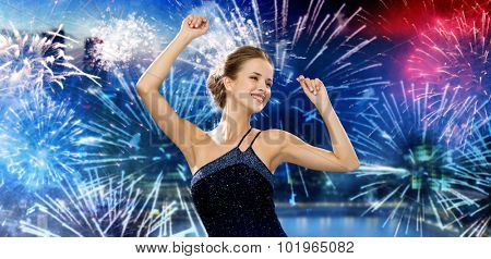 people, party, holidays and glamour concept - smiling woman dancing with raised hands over nigh city and firework background