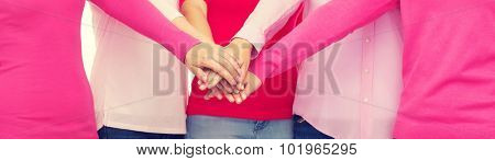 healthcare, people, gesture, breast cancer awareness and medicine concept - close up of women in pink shirts putting hands on top over white background