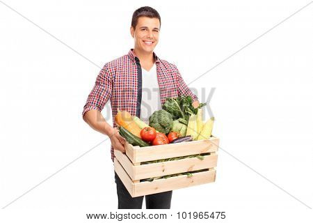 Young cheerful man carrying a wooden crate full of fresh vegetables isolated on white background
