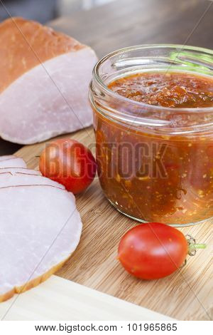 Homemade tomato sauce in glass jar with tasty ham smoked whole and sliced close-up, selective focus