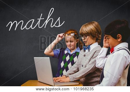 The word maths and pupils using laptop against blackboard