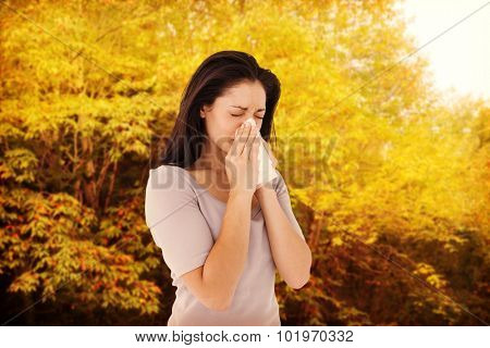 Sick brunette blowing her nose against peaceful autumn scene in forest
