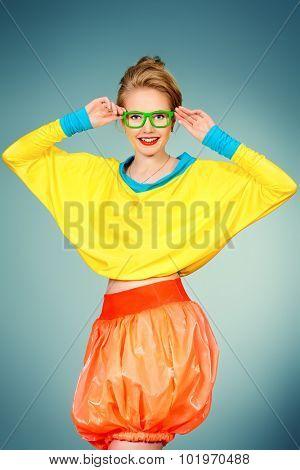 Glamorous fashion model posing in vivid colourful clothes and glasses. Bright fashion. Optics, eyewear. Studio shot.