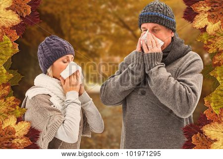 Sick mature couple blowing their noses against autumn scene