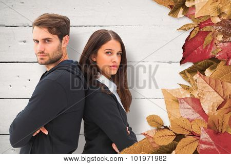 Unhappy couple not speaking to each other against white wood