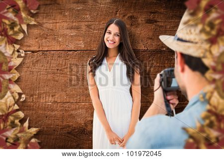 Hipster taking a photo of pretty girlfriend against overhead of wooden planks