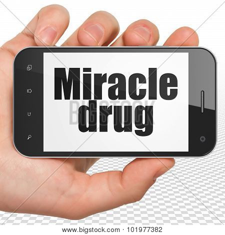 Medicine concept: Hand Holding Smartphone with Miracle Drug on display