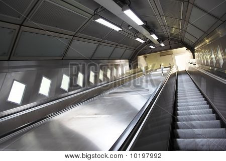 Rise on an escalator in the underground metal corridor