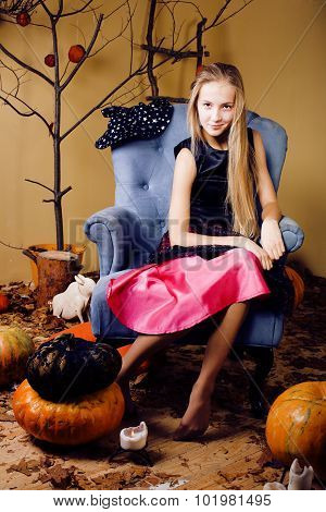 blond cute girl in halloween interior with pumpkin smiling
