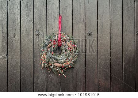 Christmas Holiday Advent wreath hanging outside at brown wooden gates background