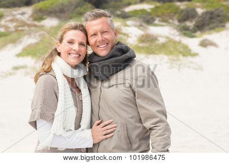 Happy couple embracing by the shore at the beach