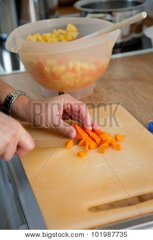Woman Chopping Carrots In The Kitchen