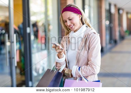 Smiling woman with shopping bags using smartphone at shopping mall