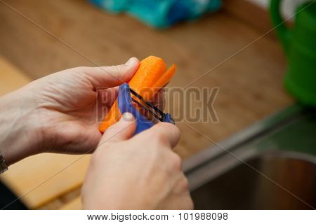 Woman Peeling Carrot In The Kitchen