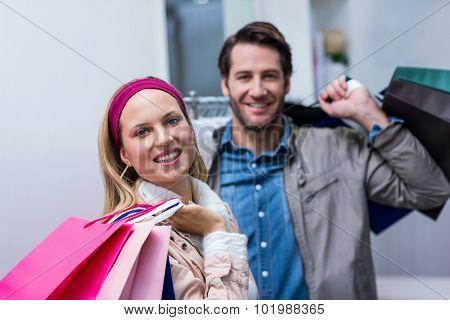 Portrait of smiling couple with shopping bags in clothing store