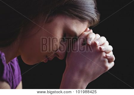 Woman praying with hands together on black background