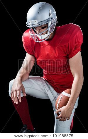 American football player with hand on knee standing against black background
