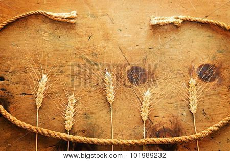 Vintage wood table with spikelets of wheat and rope