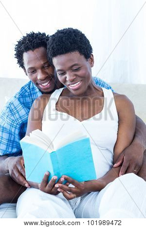 Pregnant woman and her husband reading book at home