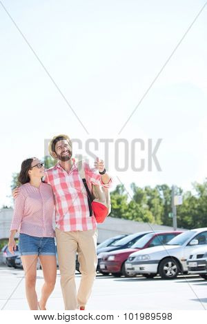 Happy couple walking on city street against clear sky