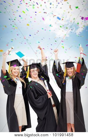 Three students in graduate robe raising their arms against blue sky