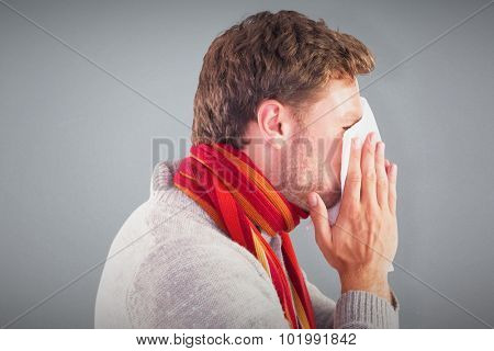 Man blowing nose on tissue against grey background