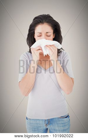 Sick brunette blowing her nose against grey background with vignette