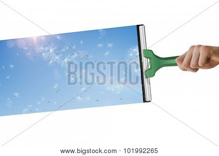 Hand using wiper against digitally generated dandelions against blue sky